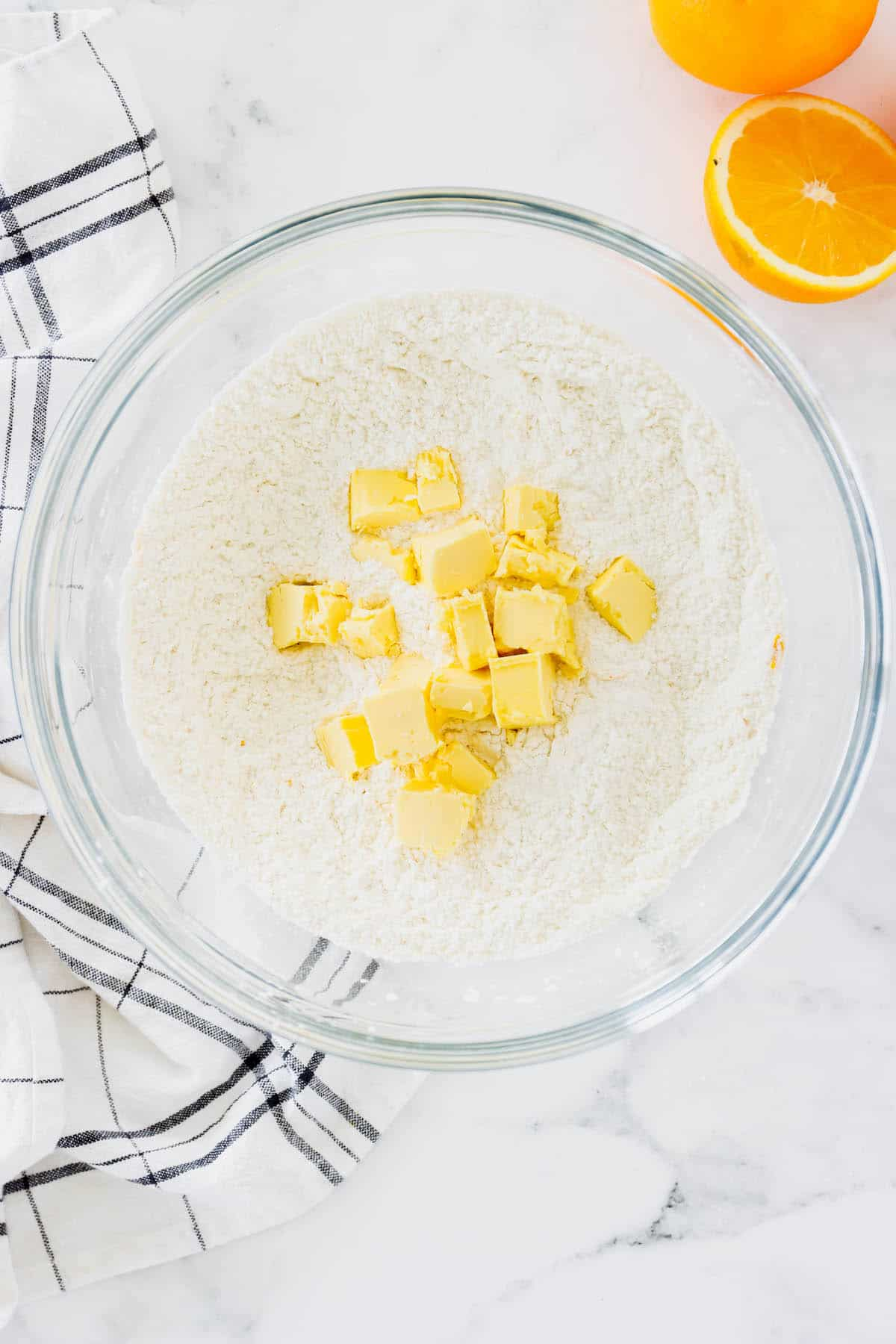 Cold butter being in a bowl of flour