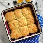 Top view of a square baking dish of blueberry cobbler with biscuit topping