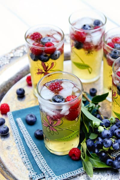 a silver tray of Passion Fruit and Berries Sparkler drinks in floral glasses