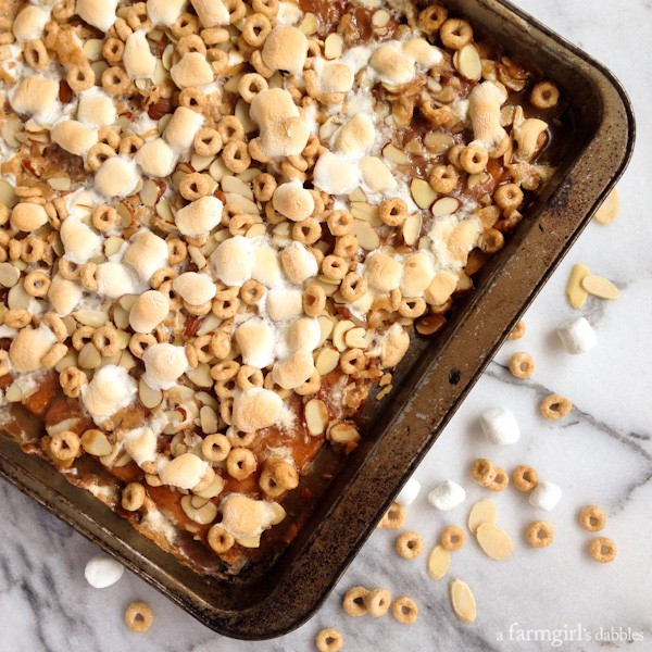 graham crackers covered in caramel, cheerios, almonds, and marshmallows