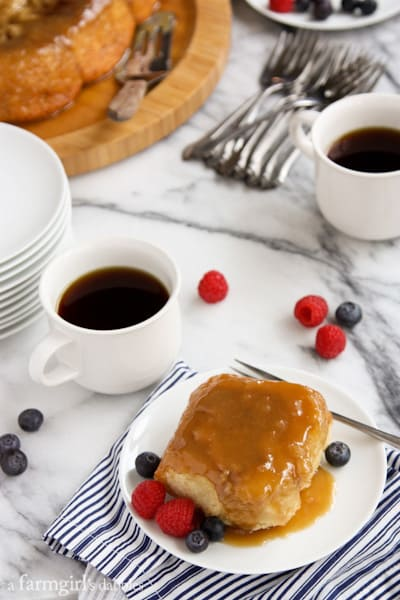 a caramel roll on a white plate with fresh berries and a cup of coffee