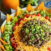 Dorito taco salad layered in a large blue bowl, with nacho cheese Doritos, lettuce, tomatoes, cheese, and taco meat