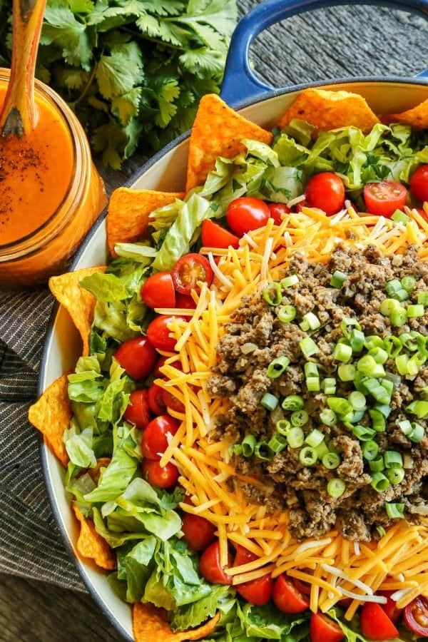 Taco Salad with Creamy Taco Dressing from afarmgirlsdabbles.com - This layered salad is bursting with fresh veggies, plus taco seasoned beef and crunchy, nacho cheese-y, irresistible Doritos.