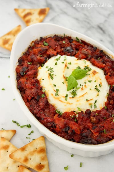 An oval baking dish of baked goat cheese surrounded by sun-dried tomato dip