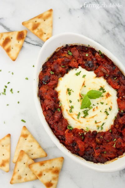 Baked Goat Cheese dip in a white, oval dish served with crackers