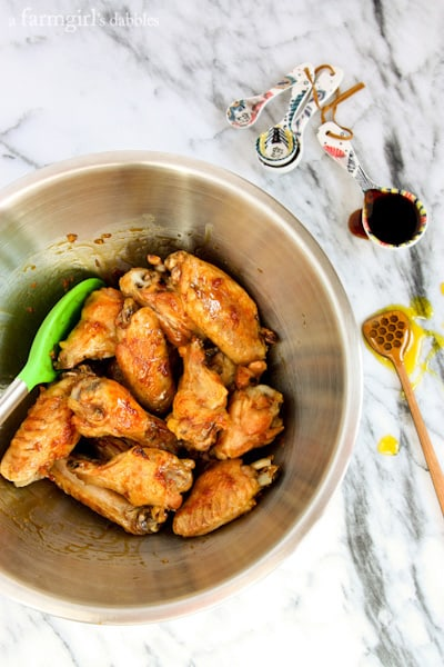 Chicken Wings being mixed with Oyster Sauce in a large metal bowl