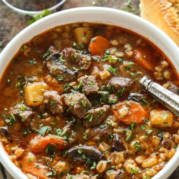 stew made with beef, barley, and vegetables - in a white bowl