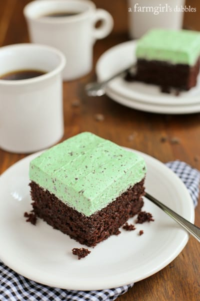 a slice of Chocolate Cake with Mint Buttercream on a white plate with a mug of coffee