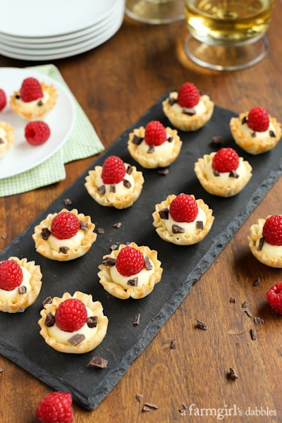 Phyllo Cups with Coconut Cream, Raspberries, and Dark Chocolate on a black board with glasses of white wine