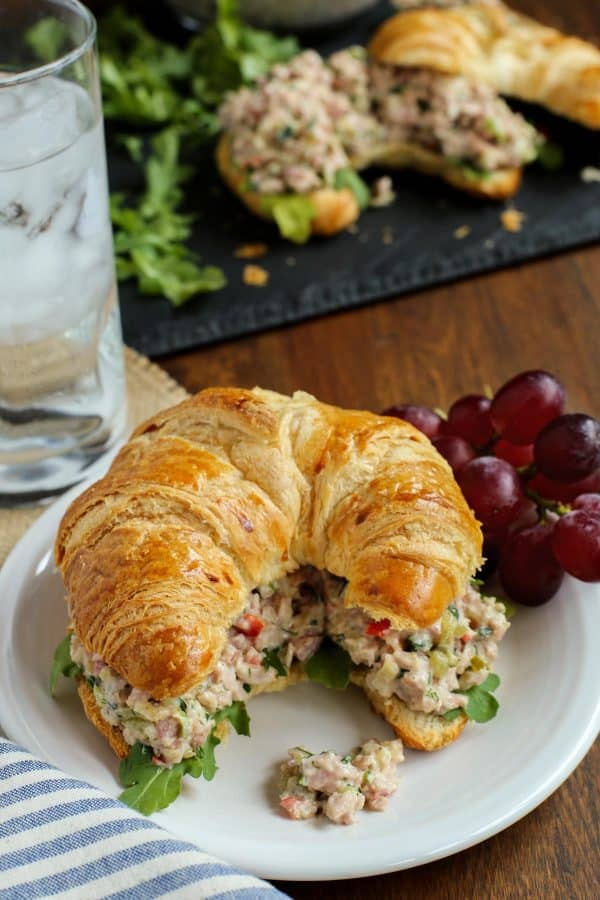 herby ham salad on a croissant with grapes and a glass of water