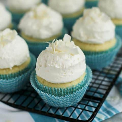 coconut cupcakes with coconut frosting on a cooling rack