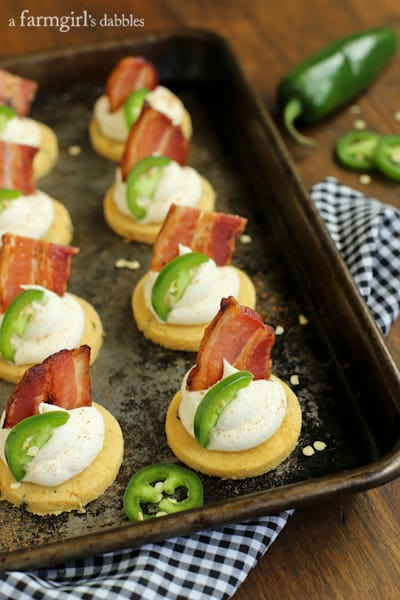 Corn Cakes topped with Honey Whipped Goat Cheese, bacon, and a slice of jalapeño