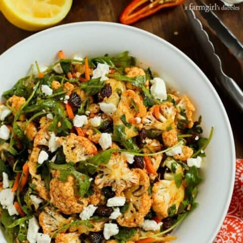 Cauliflower Salad with raisins, greens, feta and carrots in a white bowl