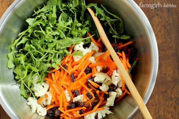 Arugula, carrots, cauliflower and raisins in a mixing bowl with a wooden spoon