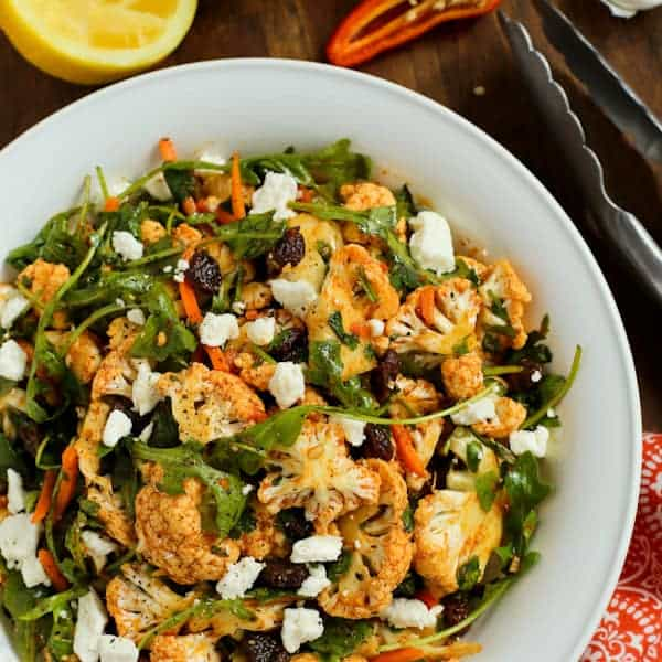 Cauliflower Salad with raisins, greens, feta and carrots in a white bowl