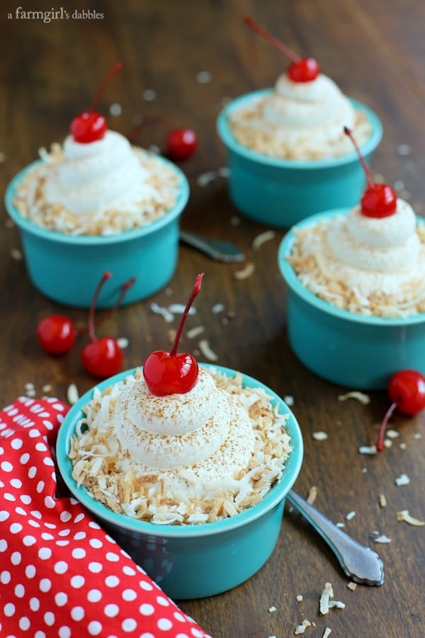 four blue Individual cups of Coconut Tres Leches Cake with whipped cream and cherries