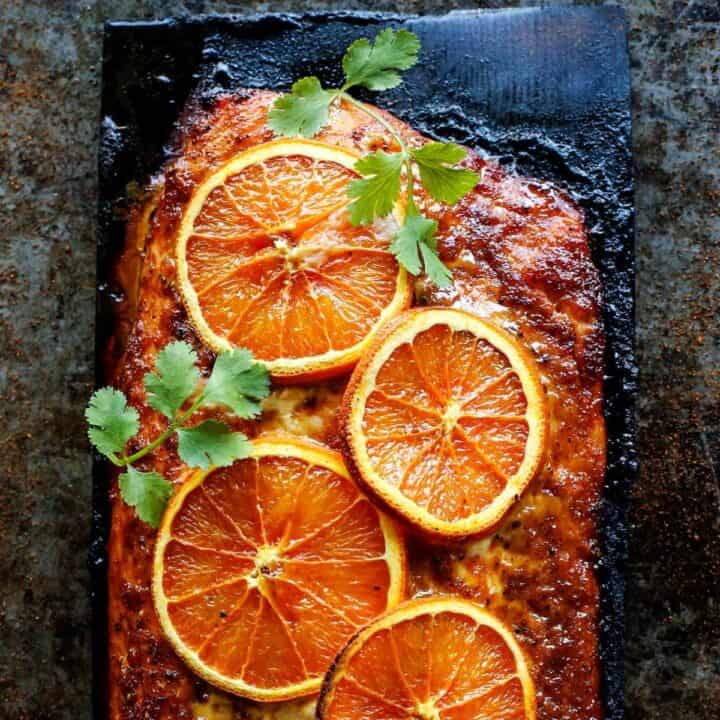 Grilled salmon with orange slices on a charred plank