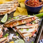 Grilled quesadilla triangles filled with crab and cheese on a baking sheet with tortilla chips and salsa