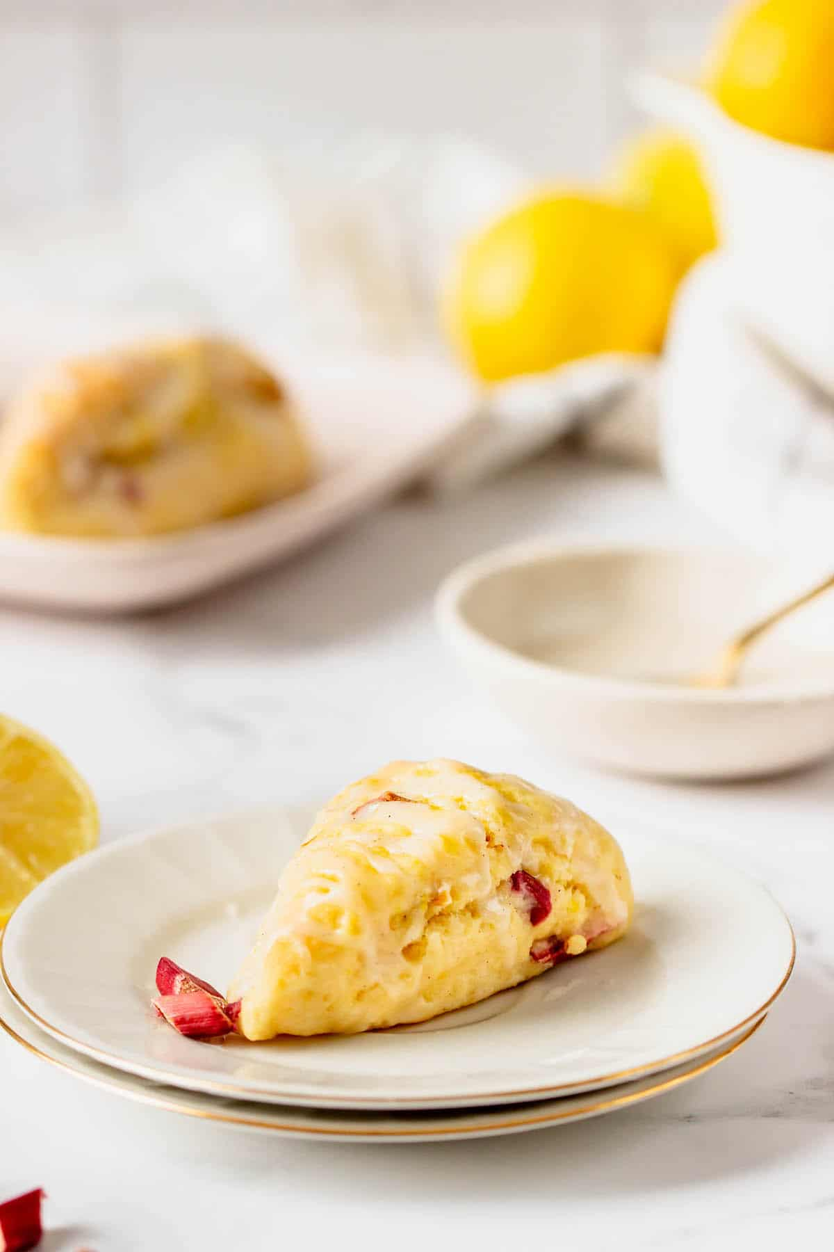 A lemon scone on a plate with another in the background