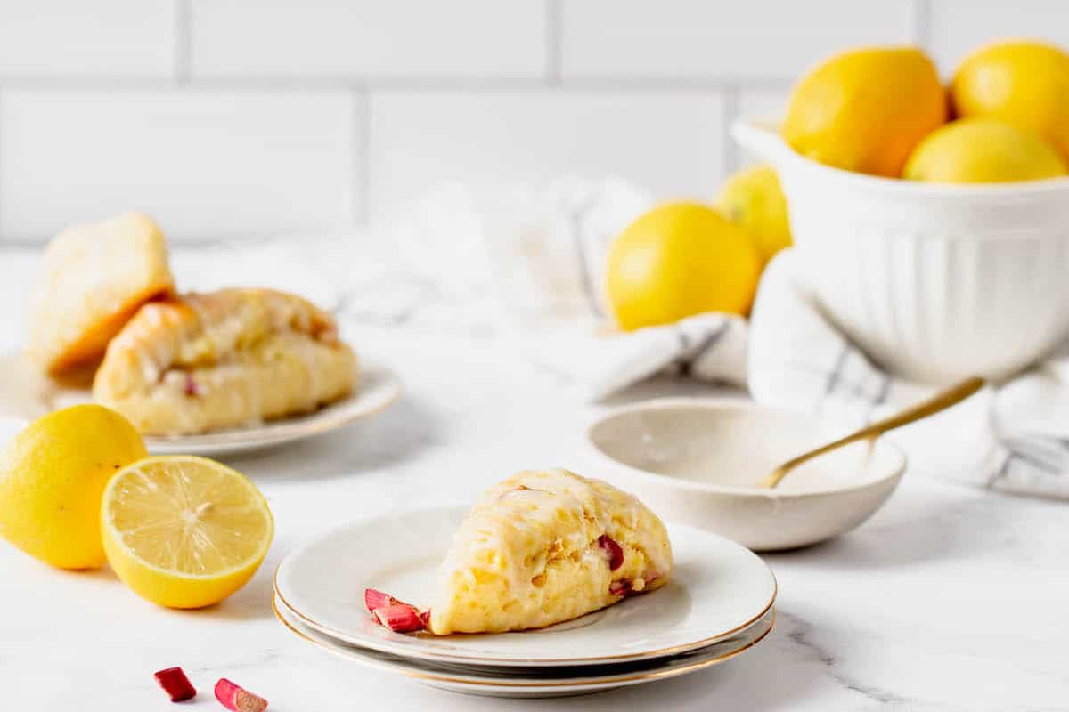 Two lemon scones on white plates, with a white bowl of lemons in the background