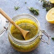 a clear jar of herby lemon vinaigrette