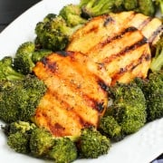 Honey mustard grilled chicken breasts on a platter with roasted broccoli