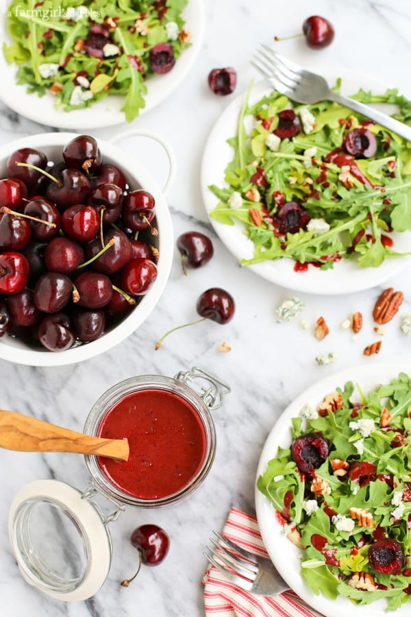 a jar of Cherry-Chipotle Balsamic Vinaigrette with small salads and a bowl of cherries