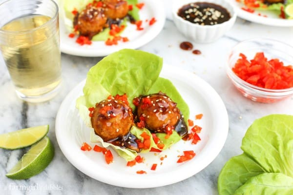 oyster Chicken Meatballs with lettuce and a glass of white wine