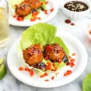 A plate of two baked chicken meatballs with oyster sauce on a bed of lettuce with diced red peppers