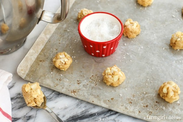 cookie dough on a baking sheet with a small red bowl of flaky sea salt