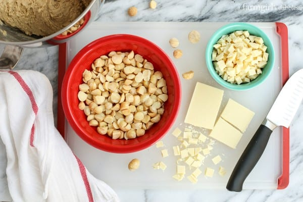 cutting board with bowls of chopped white chocolate bar and macadamia nuts