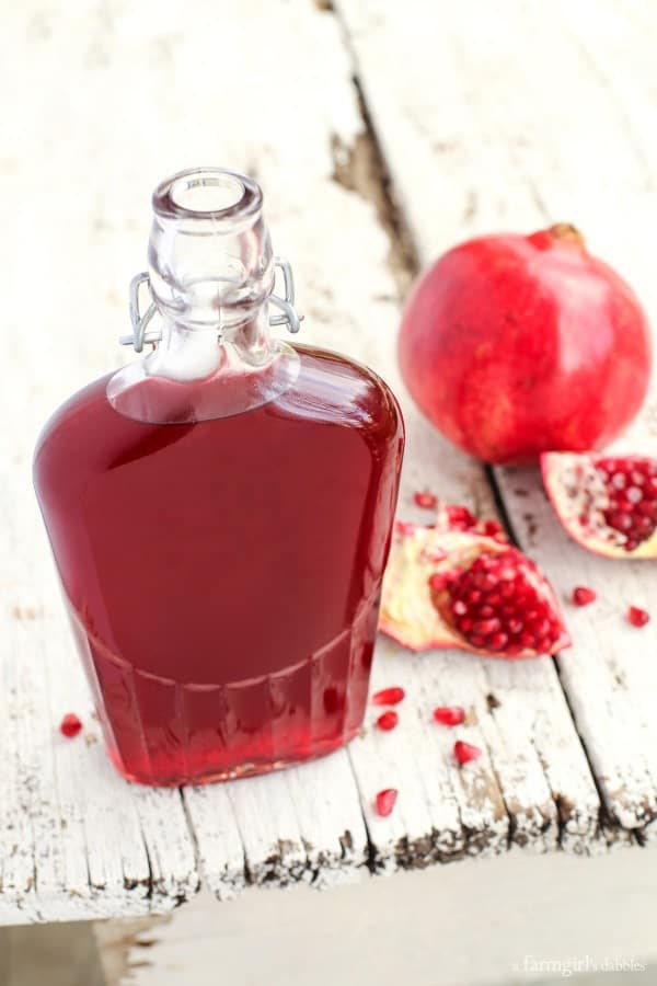 a glass bottle of pomegranate shrub with pomegranate seeds