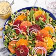 Salad with greens, sliced citrus fruit, sliced red onion and cashews on a blue plate