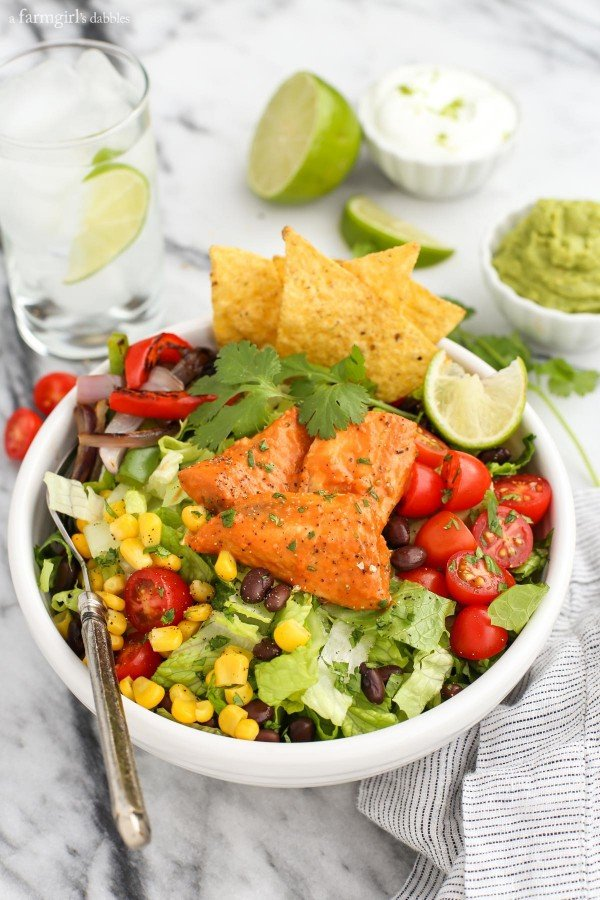 a white bowl with Santa Fe Tilapia, lettuce, corn, beans, peppers, and tomato