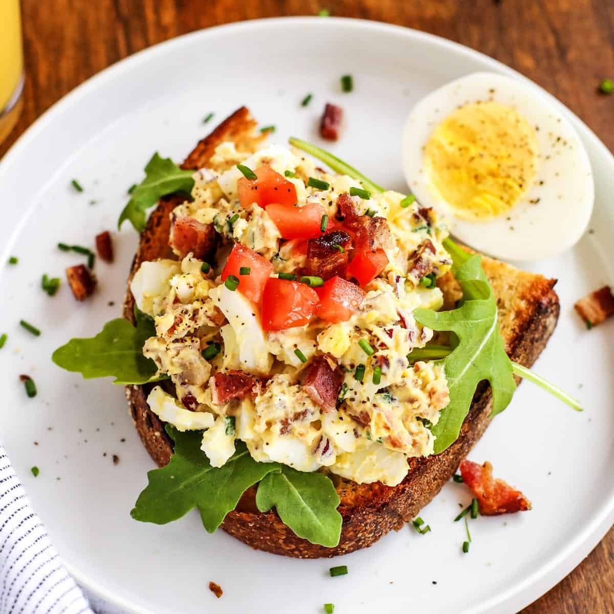 egg salad on toast, on a white plate