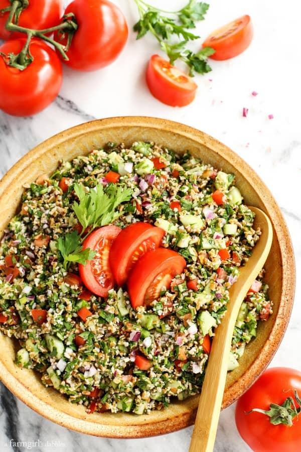 Tabbouleh in a pottery bowl with fresh tomatoes