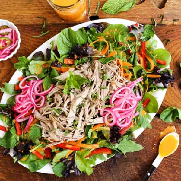 A platter of Banh Mi Salad with greens, sliced vegetables, pickled red onions, shredded meat and Sriracha vinaigrette dressing