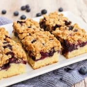 Blueberry bars with oat crumble topping on a rectangular white plate