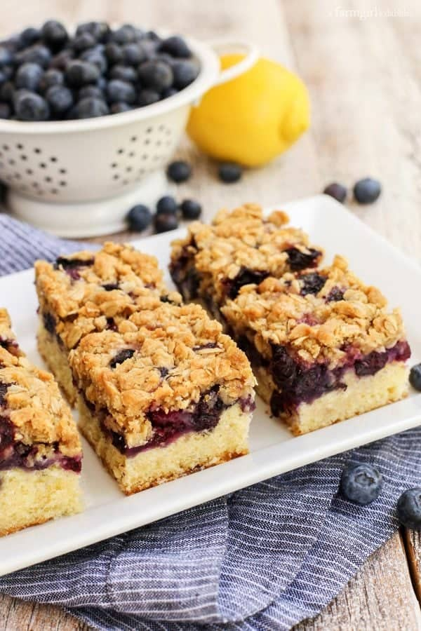 Blueberry Oat Crumble Bars on a white platter with a bowl of fresh blueberries
