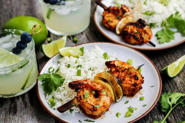 small plates of grilled shrimp skewers with white rice and fresh limes, also glasses of margaritas