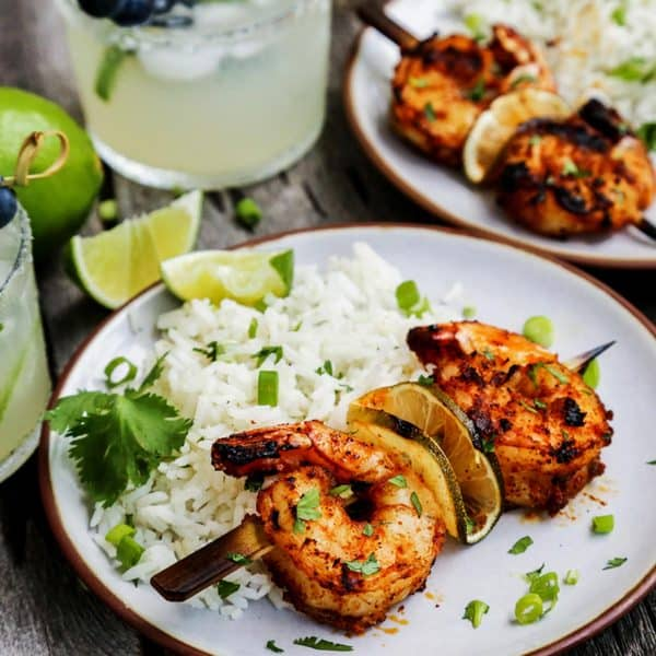 grilled shrimp skewers on plates with white rice and fresh limes, also glasses of margaritas