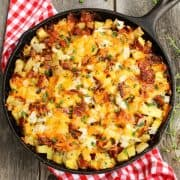 Top view of diced potatoes and bacon with melted cheese in a cast-iron skillet