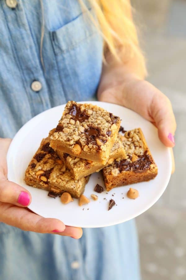 a girl holding a plate of Butterscotch Chocolate Chunk Blondies