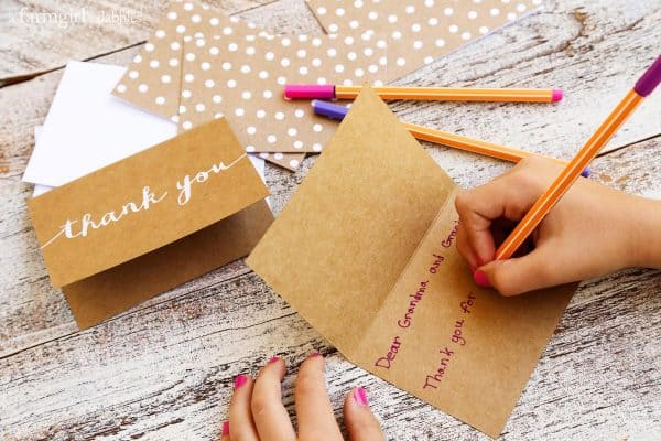 a girl writing a thank you card