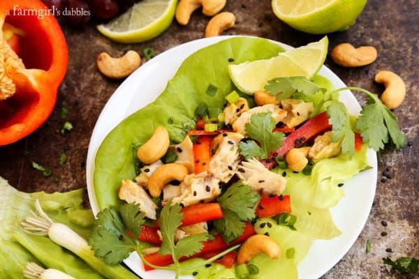 Large lettuce leaf on a plate filled with shredded tilapia, red peppers, cashews and cilantro