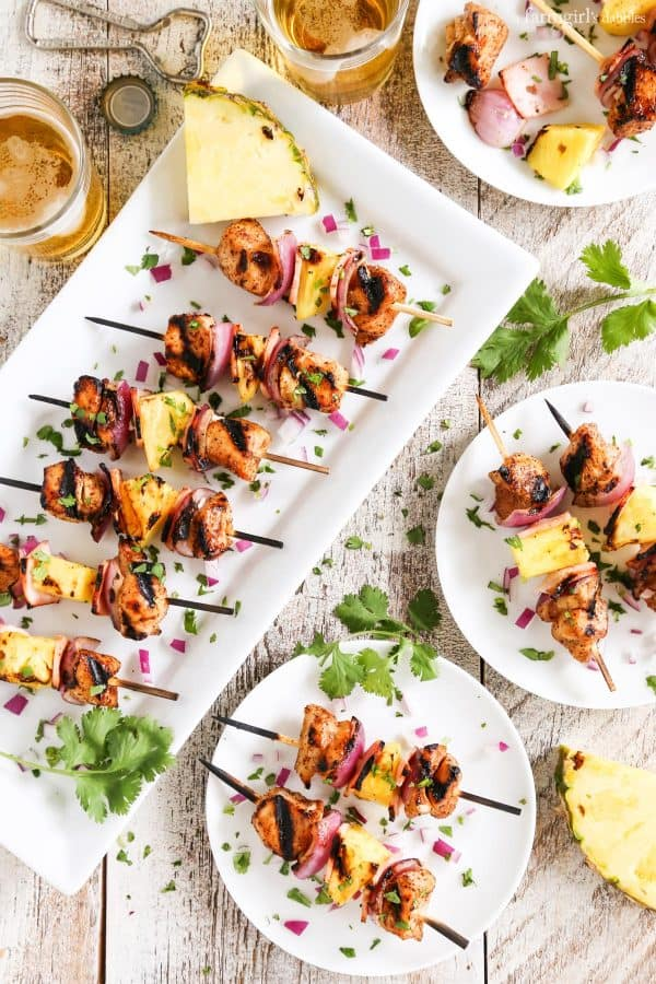 Grilled Hawaiian Chicken Chili Kebabs on a white platter and plates with glasses of beer