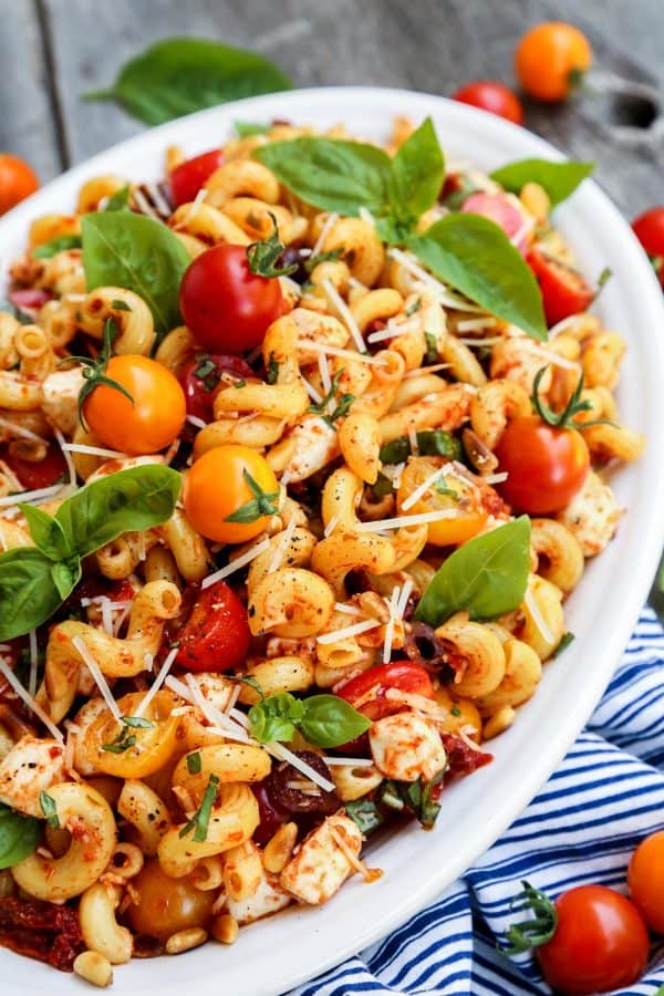 Pasta salad with sun dried tomatoes in a large, white dish