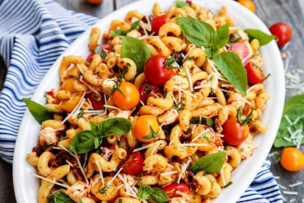 a serving bowl of full of pasta in a sun dried tomato dressing, with fresh tomatoes and basil