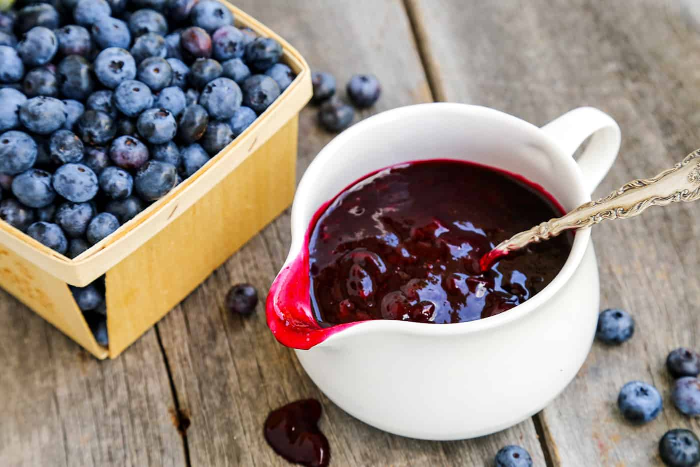 A bowl of blueberry sauce with a pint of blueberries