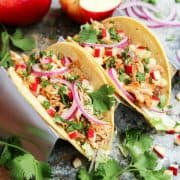 Two tacos with shredded chicken, diced apples, red onion and fresh cilantro